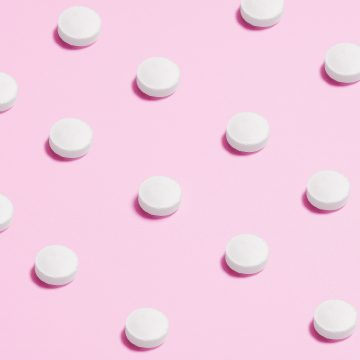 white-round-capsule-on-pink-background-close-up-photography-3683047